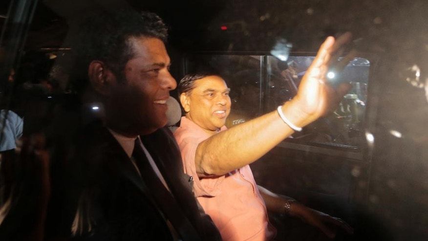 Sri Lanka's former Economic Affairs Minister Basil Rajapaksa waves to media from inside a police vehicle as he is taken to be produced before a judge in Colombo, Sri Lanka, Wednesday, April 22, 2015. Police arrested former Sri Lankan President's brother over alleged misappropriation of state funds, an official said. (AP Photo/Eranga Jayawardena)