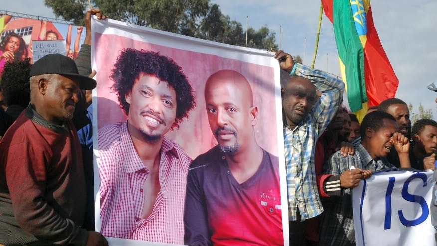 April 22, 2015: Protesters hold a banner showing victims Eyasu Yikunoamlak, left, and Balcha Belete, right, at a government-supported gathering to protest the recent killing of many Ethiopian Christians in Libya by the Islamic State extremist group, at Meskel Square in Addis Ababa, Ethiopia.