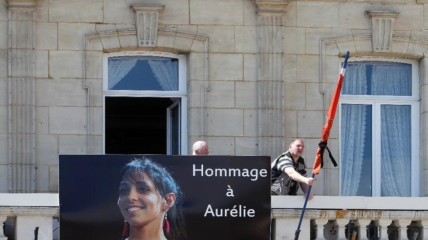Workers hang a banner showing a portrait of Aurelie Chatelain while a black ribbon is set up around the French flag on the front of the city hall of Caudry, northern France, Wednesday, April 22, 2015.  An Islamic extremist with an arsenal of loaded guns was only prevented from opening fire on churchgoers because he accidentally shot himself in the leg, French officials said Wednesday. Aurelie Chatelain, a 32-year-old Frenchwoman visiting Paris for a training session for her work, was found shot to death on Sunday morning in her car. The security official said Chatelain appeared to have been killed at random and ballistics evidence linked her death to the suspect.( AP Photo/Michel Spingler)
