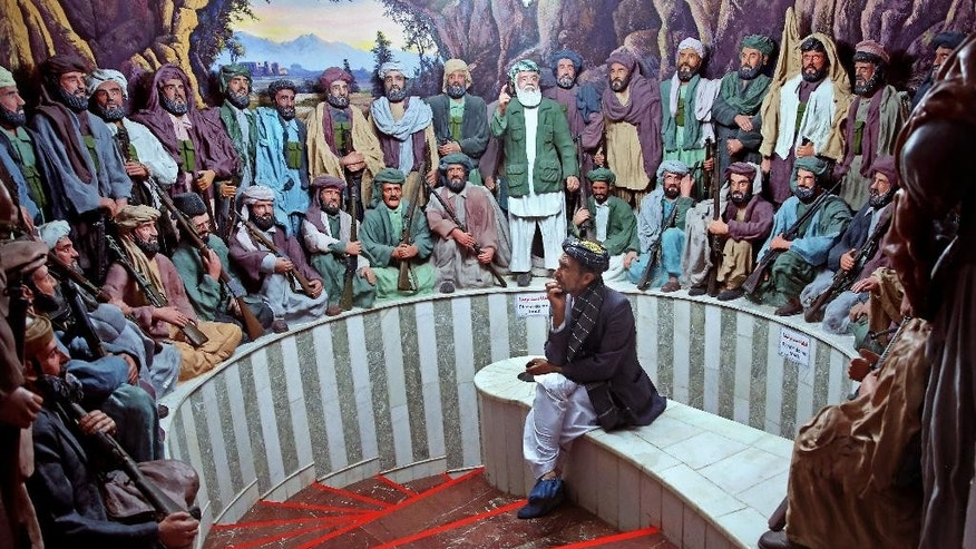 "In this Sunday, April 12, 2015 photo, tour guide Sayed Hassan, looks at statues depicting a ""Mujahideen"" gathering, at the Jihad Museum, in Herat city, west of capital Kabul, Afghanistan. Despite being an obvious homage to victory over the Soviet Union, the museum's creators say it does not seek to glorify war. The goal, they insist, is to preserve the memories of sacrifice and cruelty so future generations can avoid the painful mistakes of their forefathers. (AP Photo/Massoud Hossaini)"
