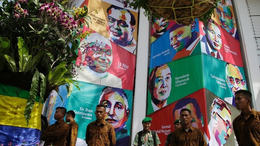 An Indonesian soldier stands guard near a building with posters of former Asian and African leaders during rehearsals for the commemoration of the 60th anniversary of the Asian African Conference in Bandung, West Java, Indonesia, Thursday, April 23, 2015. On Friday, leaders from Asia and Africa will commemorate the 60th anniversary of the formation of the Non-aligned Movement. (AP Photo/Achmad Ibrahim)