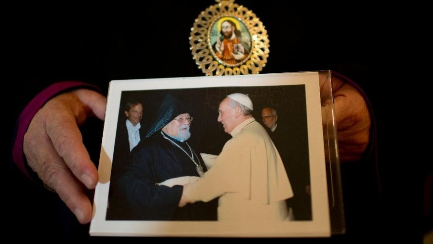 The head of the Armenian Apostolic Church in Argentina, Archbishop Kissag Mouradian holds framed photograph of him with Pope Francis in Buenos Aires, Argentina, Wednesday, April 22, 2015. Archbishop Kissag Mouradian says he developed a friendship with the pope when Jorge Mario Bergoglio was the archbishop of Buenos Aires in the 1990's. In private conversations and in public, Mouradian says Bergoglio would express support for the strong conviction of Armenians worldwide that the 1915 mass slayings in Turkey constituted genocide. (AP Photo/Natacha Pisarenko)