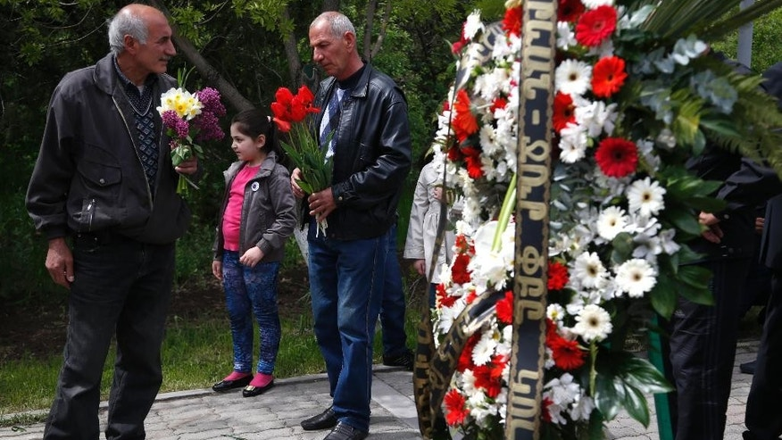 Armenians gather to lay flowers at a memorial to victims of massacres as they mark the centenary anniversary of the mass killings, in Yerevan, Armenia, Thursday, April 23, 2015. On Friday, April 24, Armenians will mark the centenary of what historians estimate to be the slaughter of up to 1.5 million Armenians by Ottoman Turks, an event widely viewed by scholars as genocide. Turkey, however, denies the deaths constituted genocide and says the death toll has been inflated. (AP Photo/Sergei Grits)
