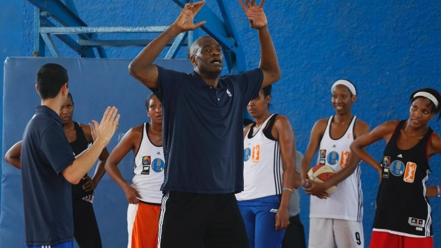 Former NBA player Dikembe Mutombo, center, and NBA Orlando Magic interim coach James Borrego, left, conduct their first NBA clinic for Cuban basketball players in Havana, Cuba, Thursday, April 23, 2015. Former Los Angeles Lakers' player Steve Nash and Mutumbo, a Hall of Fame inductee, were joined by ex-WNBA player Ticha Penicheiro and NBA coaches in teaching the more than 100 Cuban basketball athletes, hoping to boost the game's popularity on the island. (AP Photo/Desmond Boyland)