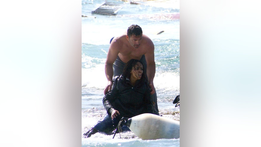 FILE - This is a Monday, April 20, 2015  file photo of a man  as he rescues  Wegasi Nebiat  an Eritrean  migrant from the Aegean sea, in the Greek island of Rhodes. Nebiat was pictured in dramatic rescue footage after sailboat carrying Syrian and Eritrean migrants sank on Monday, leaving three people dead. She was released from hospital earlier Thursday April 23, 2015 and was sailing to Greece's main port of Piraeus, near Athens.   (Argiris Mantikos/Eurokinissi via AP, File) GREECE OUT
