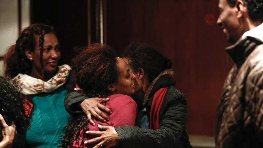 Eritrean shipwreck survivor Wegasi Nebiat , centre left,, is hugged by friends after boarding a ferry on the southeastern island of Rhodes Greece, on Thursday, April 23, 2015. Nebiat was pictured in dramatic rescue footage after sailboat carrying Syrian and Eritrean migrants sank on Monday, leaving three people dead. She was released from hospital earlier Thursday and was sailing to Greece's main port of Piraeus, near Athens. (AP Photo/Yorgos Karahalis)
