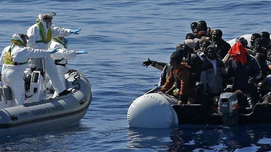 April 23, 2015: An Italian Financial Police rescue unit approaches an inflatable dinghy crowded with migrants off the Libyan coast, in the Mediterranean Sea.