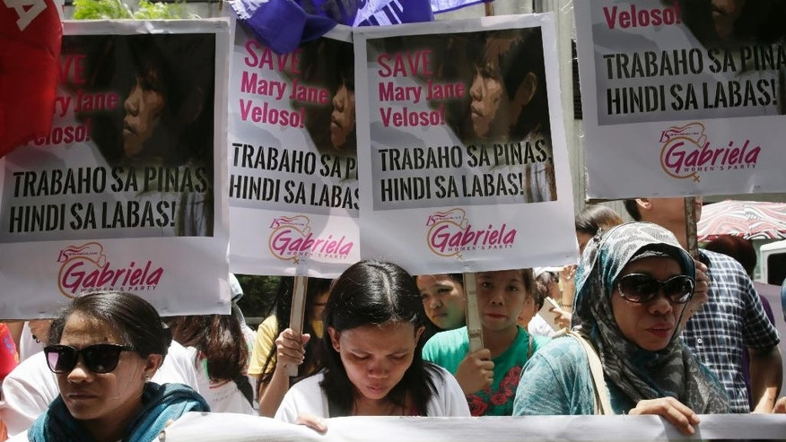 Protesters pause for a prayer as they gather outside the Indonesian Embassy in the financial district of Makati city,  east of Manila, Philippines to appeal to the Indonesian government to spare the life of convicted Filipino drug trafficker Mary Jane Veloso Friday, April 24, 2015. Filipino maid Veloso along with eight other foreign nationals and an Indonesian were sentenced to death by firing squad for illegally trafficking drugs into Indonesia in 2010. The protest came at a time as Veloso and the other convicts were transferred Friday to Nusakambangan prison island awaiting possible execution next week. (AP Photo/Bullit Marquez)