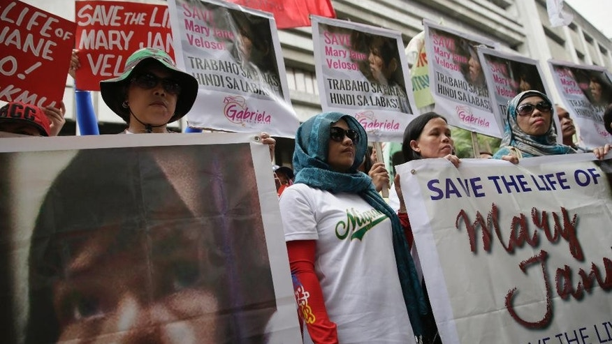 Protesters display placards during a rally at the Indonesian Embassy in the financial district of Makati city, east of Manila, Philippines, to appeal to the Indonesian government to spare the life of convicted Filipino drug trafficker Mary Jane Veloso Friday, April 24, 2015. Filipino maid Veloso along with eight other foreign nationals and an Indonesian were sentenced to death by firing squad for illegally trafficking drugs into Indonesia in 2010. The protest came at a time as Veloso and the other convicts were transferred Friday to Nusakambangan prison island awaiting possible execution next week. (AP Photo/Bullit Marquez)