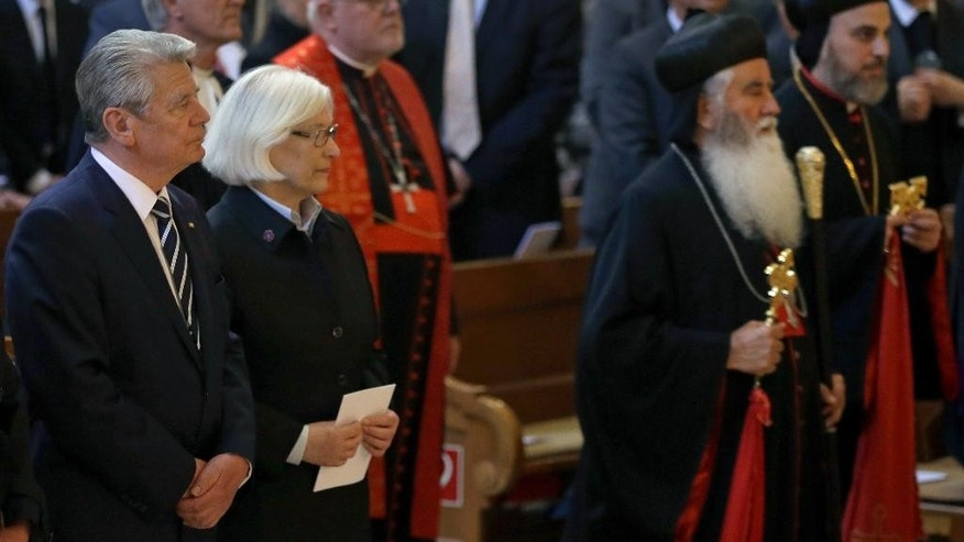 German President Joachim  Gauck, left, attends the arrival of representatives of the Armenian Apostolic church, right, for an ecumenical service remembering the Armenian slaughter at the Berlin Cathedral Church in Berlin, Germany, Thursday, April 23, 2015. On Friday, April 24, Armenians will mark the centenary of what historians estimate to be the slaughter of up to 1.5 million Armenians by Ottoman Turks, an event widely viewed by scholars as genocide. Turkey, however, denies the deaths constituted genocide and says the death toll has been inflated. (AP Photo/Michael Sohn)