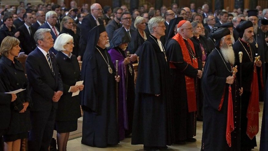 German President Joachim Gauck, second left, and his partner Dabiela Schadt, left, attend an ecumenical service remembering the Armenian slaughter at the Berlin Cathedral Church in Berlin, Germany, Thursday, April 23, 2015. On Friday, April 24, Armenians will mark the centenary of what historians estimate to be the slaughter of up to 1.5 million Armenians by Ottoman Turks, an event widely viewed by scholars as genocide. Turkey, however, denies the deaths constituted genocide and says the death toll has been inflated.  (AP Photo/Michael Sohn)
