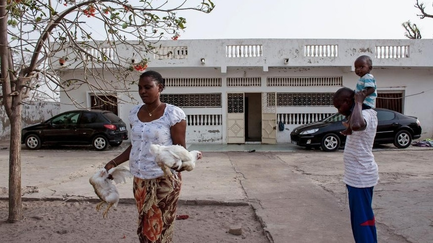 April 21, 2015: Amacoudou Ndiaye, left, walks away from  her husband Lademba Faye, right, after choosing one of two chickens that will form part of the family meal outside there home in Niakhar, Senegal.