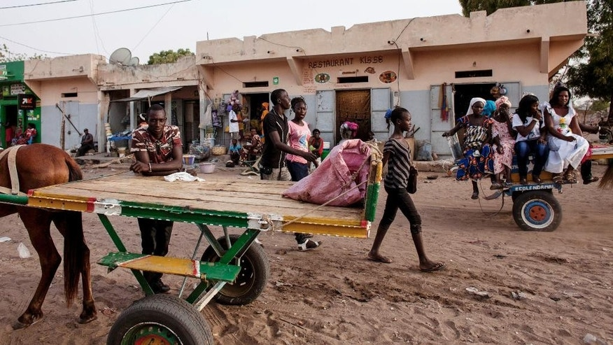 April 21, 2015: People ride on the back of a horse cart, right, on a sandy road in Niakhar, Senegal.