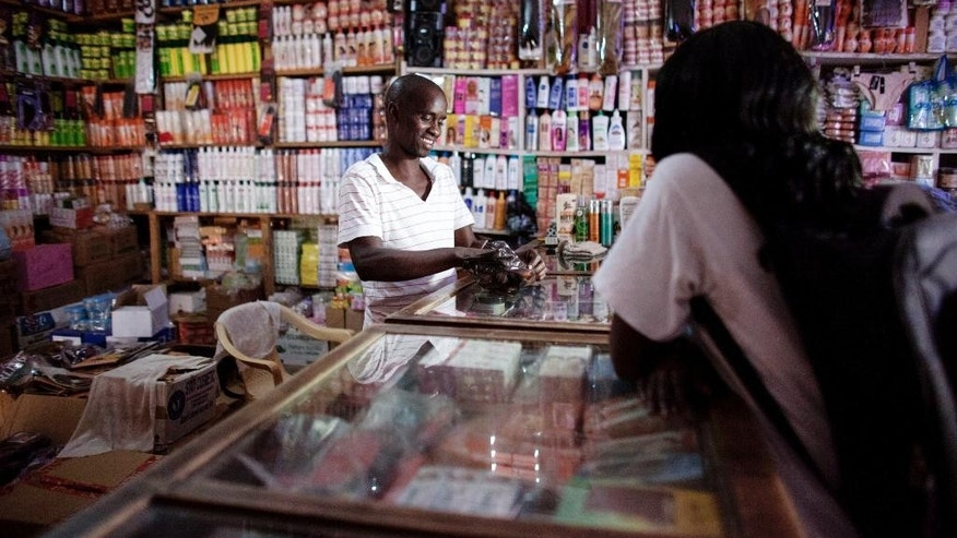 April 21, 2015: Lademba Faye, center attends to a costumer, right, inside his family owned beauty supply business in Niakhar, Senegal.