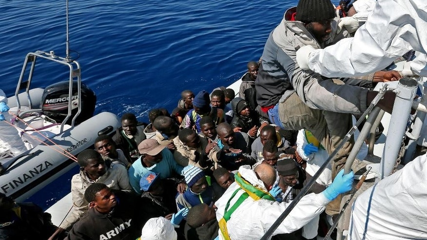 In this photo made available Thursday, April 23, 2015, members of an an Italian Financial Police unit rescue migrants off the Libyan coast after approaching an inflatable dinghy crowded with them, in the Mediterranean Sea, Wednesday, April 22, 2015.  European Union leaders gathering for an extraordinary summit are facing calls from all sides to take emergency action to save lives in the Mediterranean, where hundreds of migrants are missing and feared drowned in recent days. (Alessandro Di Meo/ANSA via AP Photo) ITALY OUT