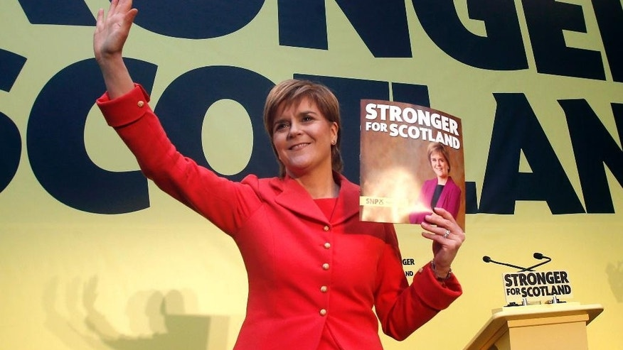 Scottish National Party leader Nicola Sturgeon holds a copy of the party's manifesto during its launch in Edinburgh, Scotland, Monday April 20, 2015. Britain will vote in a general election on May 7. (Danny Lawson/PA via AP) UNITED KINGDOM OUT  NO SALES  NO ARCHIVE  MANDATORY CREDIT