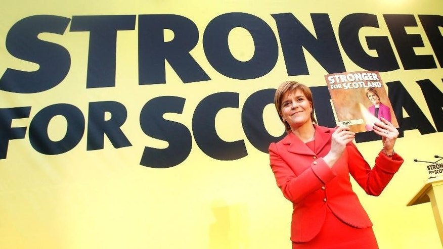 Scottish National Party leader Nicola Sturgeon holds a copy of the party's manifesto during its launch in Edinburgh, Scotland, Monday April 20, 2015. Britain will vote in a general election on May 7. (Danny Lawson/PA via AP) UNITED KINGDOM OUT  NO SALES  NO ARCHIVE