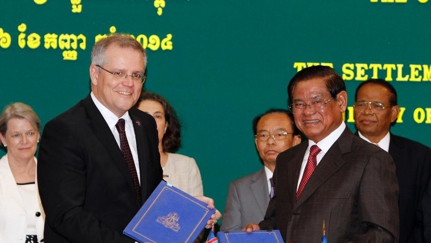 """In this Sept. 26, 2014, file photo, then Australian Immigration Minister Scott Morrison, left, shows a signed document with Cambodian Interior Minister Sar Kheng in Phnom Penh, after a deal on resettling refugees currently held at an Australian-run detention camp on the tiny Pacific island nation of Nauru. Australia has long warned the more than 700 asylum seekers it has detained on Nauru they will never be welcome on its shores. But it is now hard-selling another unlikely destination it claims offers """"a wealth of opportunity"""" to start a new life: Cambodia. (AP Photo/Heng Sinith, File)"""