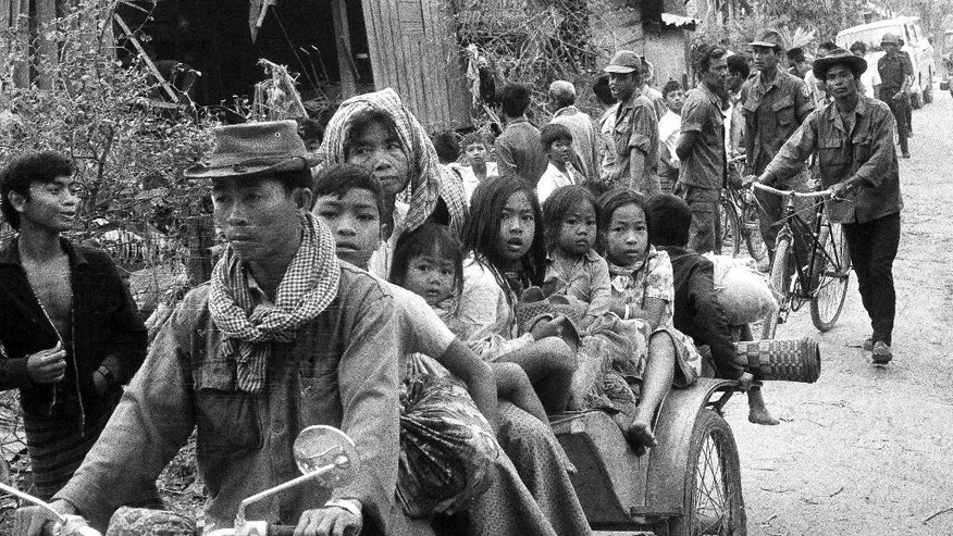 FILE - In this Jan. 28, 1974 file photo, Cambodians flee Khmer Rouge insurgents during artillery shelling of Phnom Penh. Still haunted by the Vietnam War next door and the 1970s genocide, the Southeast Asian country is not exactly the place that the world's refugees dream of reaching. Plagued by poverty, corruption and human rights abuses, it has been run by a strongman prime minister who has held power for 30 years. It's a nation where medical care outside main cities is nonexistent, where decent jobs are so scarce that more than 800,000 of its own people have left to find work abroad. (AP Photo, File)