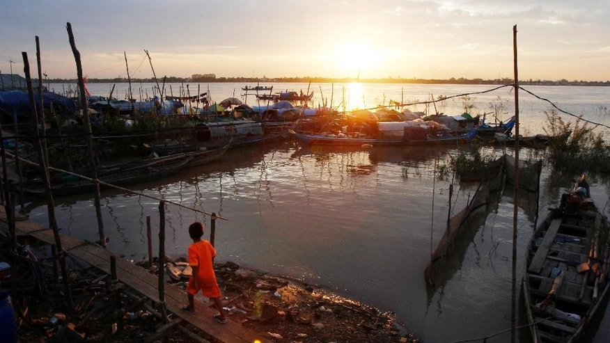 """In this Aug. 17, 2014, file photo, a Cambodian boy walks across a bamboo bridge at the fishing village of Tuol Yey Ma along the Mekong River bank near Phnom Penh, Cambodia. Australia has long warned the more than 700 asylum seekers it has detained on the remote Pacific Island nation of Nauru they will never be welcome on its shores. But it is now hard-selling another unlikely destination it claims offers """"a wealth of opportunity"""" to start a new life: Cambodia. (AP Photo/Heng Sinith, File)"""