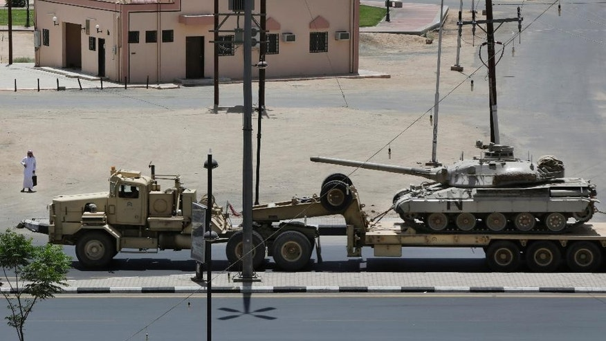 A Saudi man looks at an army tank being transported, in the city of Najran, Saudi Arabia, near the border with Yemen, Thursday, April 23, 2015. In a stunning development, Saudi Arabia had declared on Tuesday, April 21, 2015 that it was halting coalition airstrikes targeting Yemen's Shiite rebels known as Houthis — a four-week air campaign meant to halt the rebel power grab and help return to office embattled President Abed Rabbo Mansour Hadi, a close U.S. ally who fled Yemen. (AP Photo/Hasan Jamali)