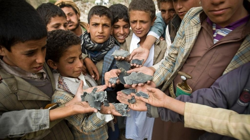 FILE - In this Saturday, April 4, 2015, file photo, Yemeni boys display shrapnel they collected from the rubble of houses destroyed by Saudi-led airstrikes in a village near Sanaa, Yemen. With the combatants pounding each other in residential areas and Saudi-led coalition warplanes bombarding from the sky, Yemen's war is wreaking a particularly bloody toll among civilians: more than 550 dead the past month, including at least 115 children, according to the UN. So far, relatively muted international outcry has put little pressure on the warring sides to stop. (AP Photo/Hani Mohammed, File)