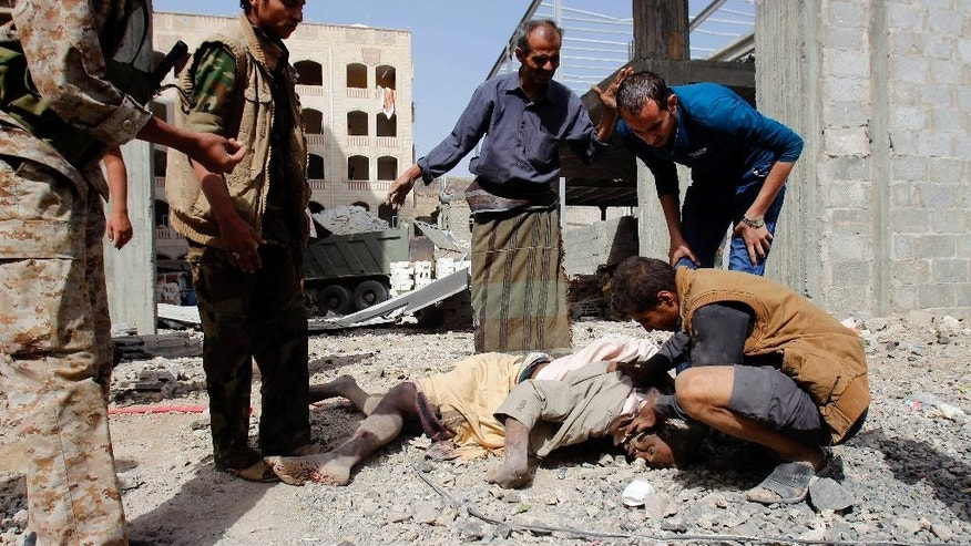 FILE - In this Monday, April 20, 2015, file photo, Yemenis check the body of a man killed in a Saudi-led airstrike against Iran-allied Shiite rebels, known as Houthis, that hit a site of a weapons cache in Yemen's capital, Sanaa. With the combatants pounding each other in residential areas and Saudi-led coalition warplanes bombarding from the sky, Yemen's war is wreaking a particularly bloody toll among civilians: more than 550 dead the past month, including at least 115 children, according to the UN. So far, relatively muted international outcry has put little pressure on the warring sides to stop. (AP Photo/Hani Mohammed, File)