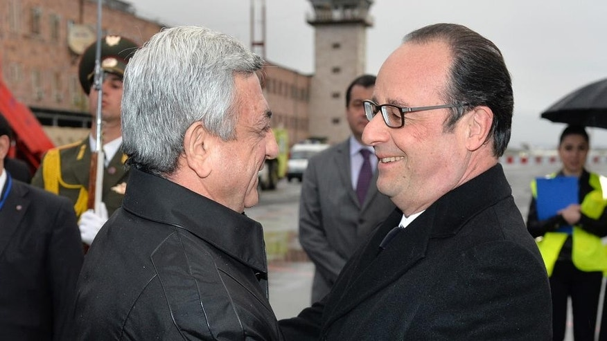 Armenia's President Serge Sarkisian, left, welcomes French President Francois Hollande at Zvartnots airport outside the capital, Yerevan, Armenia, early Friday, April 24, 2015. World leaders are attending ceremonies Friday commemorating the massacre 100 years ago of 1.5 million Armenians by Ottoman Turks. The event around the time of the World War I is widely viewed by historians as genocide. Modern Turkey, the successor to the Ottoman Empire, vehemently rejects the charge. (Davit Hakobyan/PAN Photo via AP)