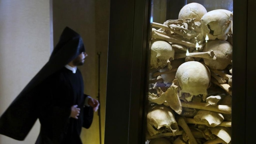 A Lebanese priest of Armenian descent passes by human remains of people killed in 1915 inside an Armenian church as many in Lebanon marked the 100th anniversary of the mass killings of Armenians by Ottoman Turks around the time of World War I, in Antelias, north of Beirut, Lebanon, Friday, April 24, 2015. Historians estimate up to 1.5 million Armenians were killed, an event widely viewed by genocide scholars as the first genocide of the 20th century. Turkey, however, denies the deaths constituted genocide, saying the toll has been inflated and that those killed were victims of civil war and unrest. (AP Photo/Bilal Hussein)
