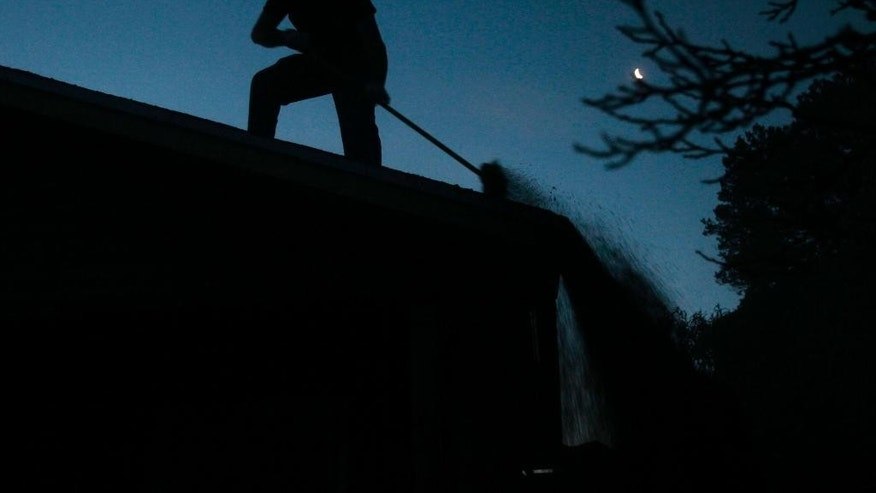 A man sweeps volcanic ash deposited from the eruption of the Calbuco Volcano, from the roof of a house in Puerto Varas, Chile, Thursday, April 23, 2015. Due to the eruption the Chilean government has declared a state of emergency in the region surrounding the volcano, including the cities of Puerto Montt and Puerto Varas, and handed over civil authority to the armed forces. (AP Photo/Luis Hidalgo)