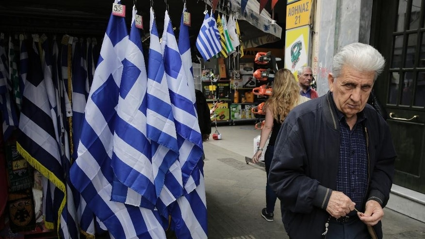 An man walk past a kiosk with Greek flags for sale in central Athens, Thursday, April 23, 2015. Greece is running perilously short of cash amid an impasse in bailout talks with its international creditors. Eurozone finance ministers are to meet in Riga, Latvia on Friday but hopes of a deal on Greece there have diminished. (AP Photo/Petros Giannakouris)