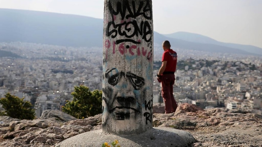 A man watches the city of Athens at Filopalous hill, on Friday, April 24, 2015. Time is running out for Greece to reach a deal with bailout creditors and prevent the country going bankrupt, the eurozone's top official said Friday as he headed into discussions with his colleagues from the 19-country single currency zone. (AP Photo/Petros Giannakouris)