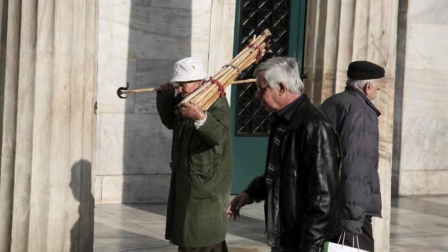 A street vendor carries handmade canes past the Athens' municipality building in central Athens, on Friday April 24, 2015. Time is running out for Greece to reach a deal with bailout creditors and prevent the country going bankrupt, the eurozone's top official said Friday as he headed into discussions with his colleagues from the 19-country single currency zone. (AP Photo/Petros Giannakouris)