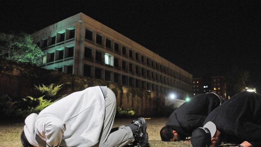 Three freed Guantanamo Bay detainees, who were resettled in Uruguay, pray during their protest outside the U.S. embassy in Montevideo, Uruguay, Friday, April 24, 2015. From left to right Omar Abdelahdi Faraj and Ali Husain Shaaban, both of Syria, and Adel bin Muhammad El Ouerghi of Tunisia. The men are protesting after they were asked to leave a hotel where some stayed periodically, and demand Washington help them financially. They say the house where they were initially resettled didn't have enough space for all of them. The men spent 12 years at the U.S. military prison but were never charged, and were released after officials determined they were no longer a threat. (AP Photo/Nicolas Garrido) URUGUAY OUT - NO PUBLICAR EN URUGUAY