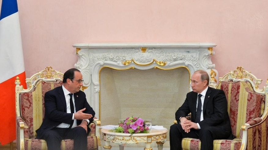 Russian President Vladimir Putin, right, and French President Francois Hollande speak during their meeting in Yerevan, Armenia, Friday, April 24, 2015. The presidents of Russia and France joined other leaders Friday at ceremonies commemorating the massacre of Armenians a century ago by Ottoman Turks, an event which still stirs bitter feelings as both sides argue over whether to call it genocide. (Davit Hakobyan/Presidential Press Service, PAN Photo Pool via AP)