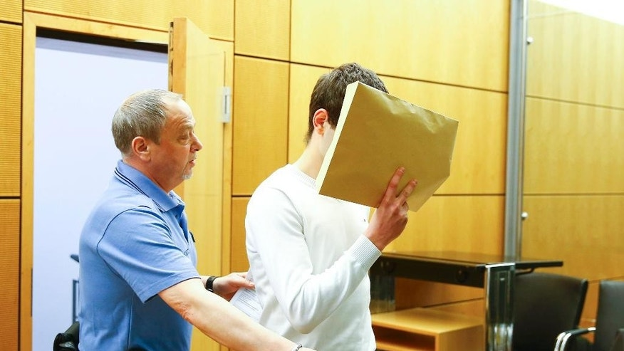 Defendant Sanel M. (no family name given according with German privacy law) covers his face as he arrives in the courtroom for the start of his trial in Darmstadt, Germany, Friday April 24, 2015. The 18-years-old man is accused of punching student Tugce Albayrak in November 2014 in front of a fast food shop in Offenbach near Frankfurt. The student died a few days later. (Kai Pfaffenbach/Pool Photo via AP)