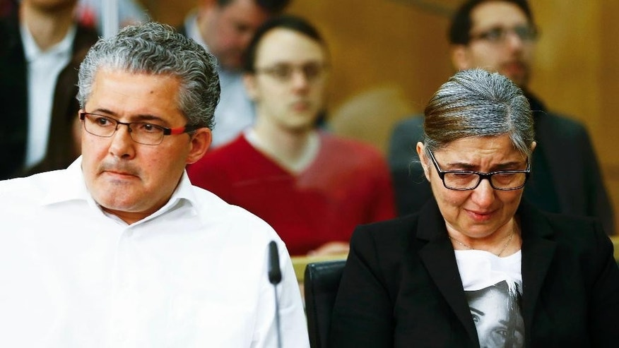 Ali Albayrak, left, father of killed student Tugce, and her mother wait for the beginning of the trial against an 18-years-old man in Darmstadt, Germany, Friday April 24, 2015. He is accused of punching student Tugce Albayrak in November 2014 in front of a fast food shop in Offenbach near Frankfurt. The student died a few days later. (Kai Pfaffenbach/Pool Photo via AP)