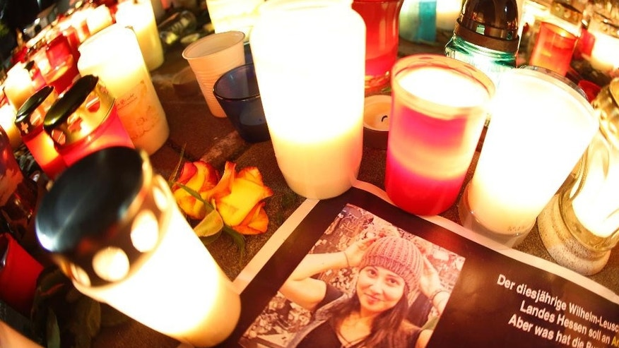 FILE - In this Nov. 29, 2014 file photo candles are lit next to a photograph of Tugce, in front of the hospital in Offenbach, Germany, Saturday, Nov. 29, 2014. Thousands paid tribute to the student who was beaten to death after she tried to help two other girls outside a fast food branch. The trial against the man who had beaten her started Friday, April 24, 2015. (AP Photo/Michael Probst, file)