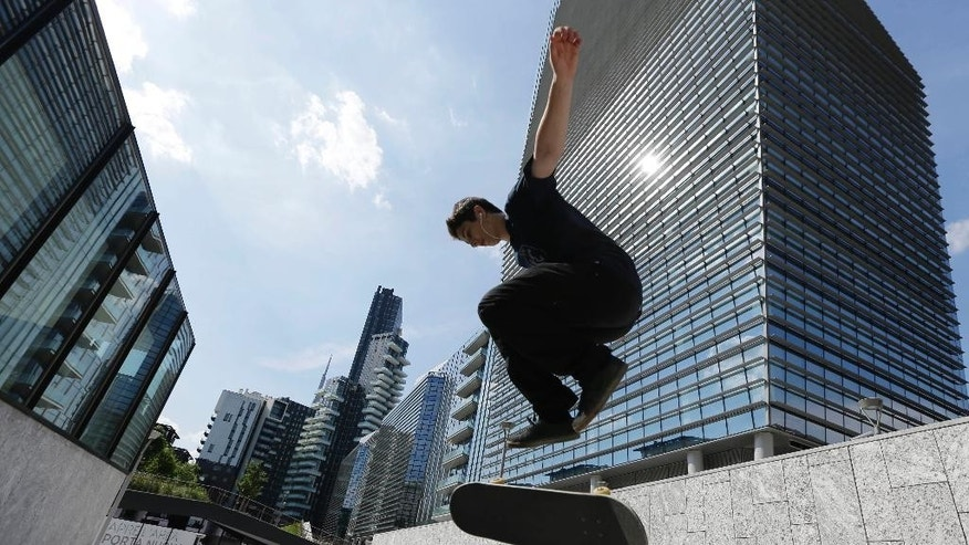 In this photo taken on Friday, May 30, 2014, a boy takes a jump as he performs on a skateboard in Milan, Italy. Milan has been growing in altitude in preparation for Expo 2015 world's fair opening next Friday, May 1, 2015 with the construction of a dozen new skyscrapers in recent years that have permanently altered the skyline. City leaders hope a successful world's fair, expected to attract 20 million visitors from across the globe over the six-month run, will help Italy's fashion and banking capital grow in international stature, as well. (AP Photo/Luca Bruno)