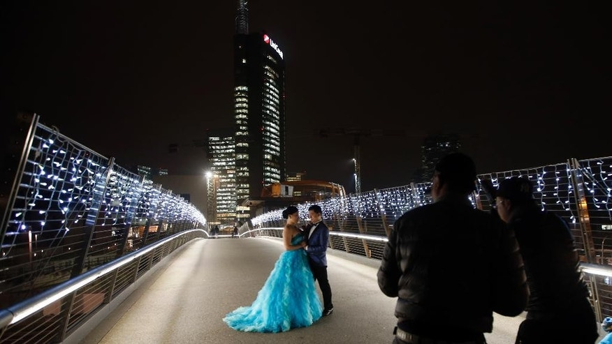 FILE - In this Friday, Dec. 5, 2014 file photo, a just married Chinese couple pose for pictures on a bridge leading to the Porta Nuova business district in Milan, Italy. Milan has been growing in altitude in preparation for Expo 2015 world's fair opening next Friday, May 1, 2015 with the construction of a dozen new skyscrapers in recent years that have permanently altered the skyline. City leaders hope a successful world's fair, expected to attract 20 million visitors from across the globe over the six-month run, will help Italy's fashion and banking capital grow in international stature, as well. (AP Photo/Luca Bruno, File)