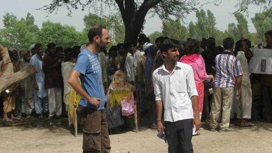 "In this May 28, 2011 photo provided by Margherita Romanelli and made available Thursday, April 23, 2015, Italian aid worker Giovanni Lo Porto, left, works in Multan, Pakistan. The Italian government on Thursday deplored the death of an Italian aid worker in a U.S. air strike, calling it a ""fatal error"" by the Americans. Italian Premier Matteo Renzi expressed his ""profound pain"" over Giovanni Lo Porto's death and offered Italy's condolences to Lo Porto's family and that of American Warren Weinstein, who was killed in the same airstrike on the border between Pakistan and Afghanistan. Both were held hostage by al-Qaida. (Andrea Parisi/Courtesy of Margherita Romanelli via AP)"