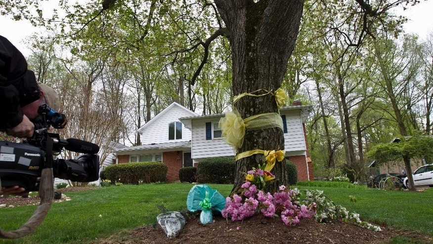 "A cameraman photographs flowers and ribbon on a tree outside Weinstein family house in Rockville, Md., Thursday, April 23, 2015. Earlier, President Barack Obama took full responsibility for the counterterror missions and offered his ""grief and condolences"" to the families of the hostages, Warren Weinstein of Rockville, Maryland, and Giovanni Lo Porto who were inadvertently killed by CIA drone strikes early this year. (AP Photo/Jose Luis Magana)"