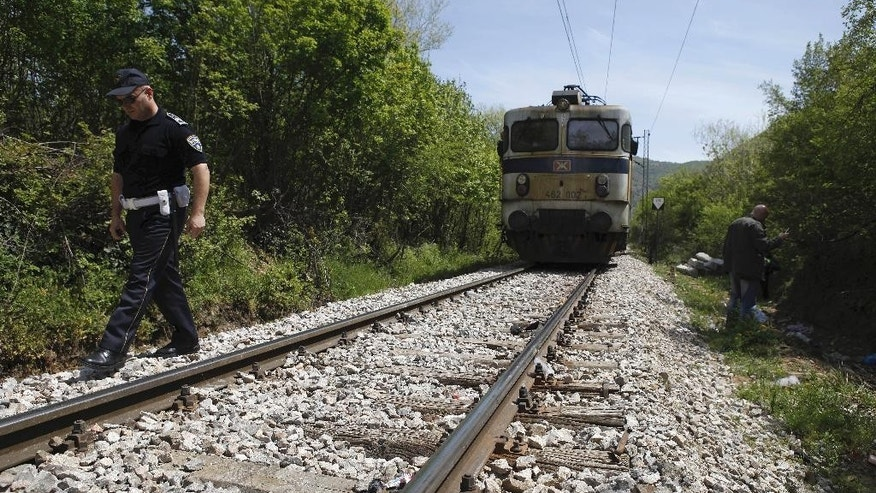 A police officer walks along the rail tracks north of the central Macedonian town of Veles, on Friday, April 24, 2015 near where 14 migrants were killed by a train while walking along the tracks. Fourteen migrants believed to be from Afghanistan and Somalia who were heading north toward the European Union were killed by an express train as they walked along tracks in central Macedonia Thursday night, police said Friday. (AP Photo/Boris Grdanoski)