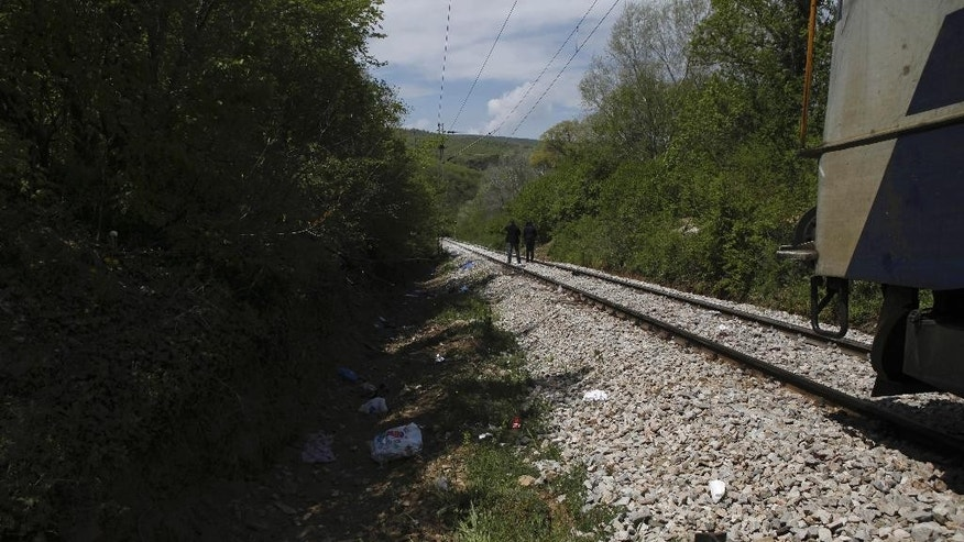 A train stops on the rail tracks north of the central Macedonian town of Veles, on Friday, April 24, 2015 near where 14 migrants were killed by a train while walking along the tracks. Fourteen migrants believed to be from Afghanistan and Somalia who were heading north toward the European Union were killed by an express train as they walked along tracks in central Macedonia Thursday night, police said Friday. (AP Photo/Boris Grdanoski)