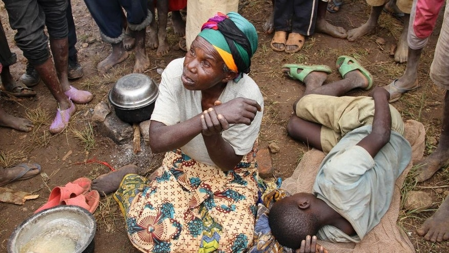 In this photo taken Tuesday, April 21, 2015, Burundian refugee Laeticia Mukankuranga, 67, writhes in pain due to her arm which was broken when she slipped and fell while escaping a group of youth who were blocking her from exiting Burundi with her sick grandchild, at the Gashora refugee camp, in the Bugesera district of Rwanda. More than 10,000 people from the East African nation of Burundi have crossed into neighboring Rwanda amid threats of violence ahead of elections, with many arriving saying they have been intimidated by thugs who support President Pierre Nkurunziza who may seek a third term. (AP Photo/Edmund Kagire)