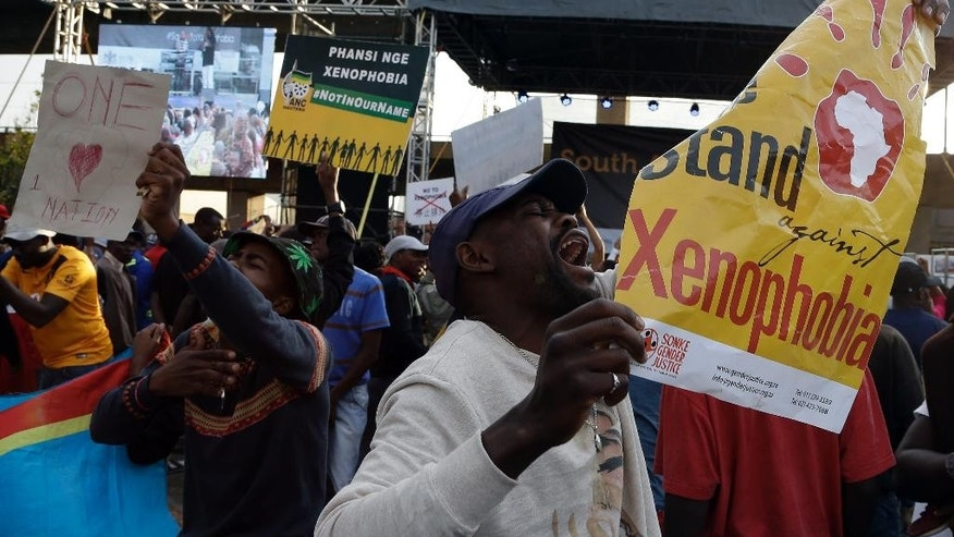 "A man holding a poster reading ""we stand against xenophobia"" shouts slogans during a march in Johannesburg, South Africa, Thursday, April 23, 2015, protesting against recent attacks on immigrants that killed seven people. The protesters walked through the center of Johannesburg passing neighborhoods that are home to many immigrants, a large number of whom come from other African countries. (AP Photo/Themba Hadebe )"