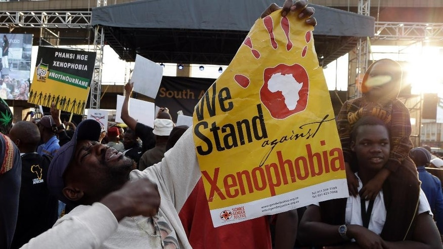 "A man holds a poster reading ""we stand against xenophobia""  during a march in Johannesburg, South Africa, Thursday, April 23, 2015, protesting against recent attacks on immigrants that killed seven people. The protesters walked through the center of Johannesburg passing neighborhoods that are home to many immigrants, a large number of whom come from other African countries. ( AP Photo/Themba Hadebe )"
