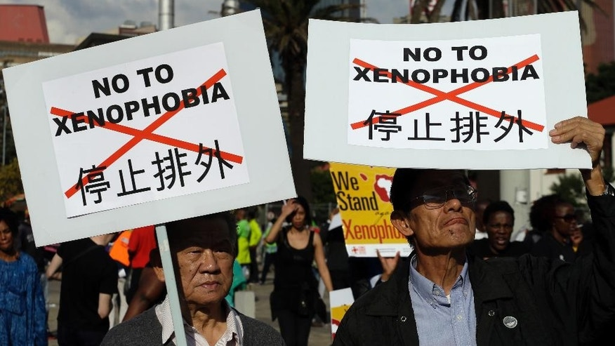 "Asian nationals hold placards reading ""no to xenophobia"" during a march in Johannesburg, South Africa, Thursday, April 23, 2015, protesting against recent attacks on immigrants that killed seven people. The protesters walked through the center of Johannesburg passing neighborhoods that are home to many immigrants, a large number of whom come from other African countries. ( AP Photo/Themba Hadebe )"