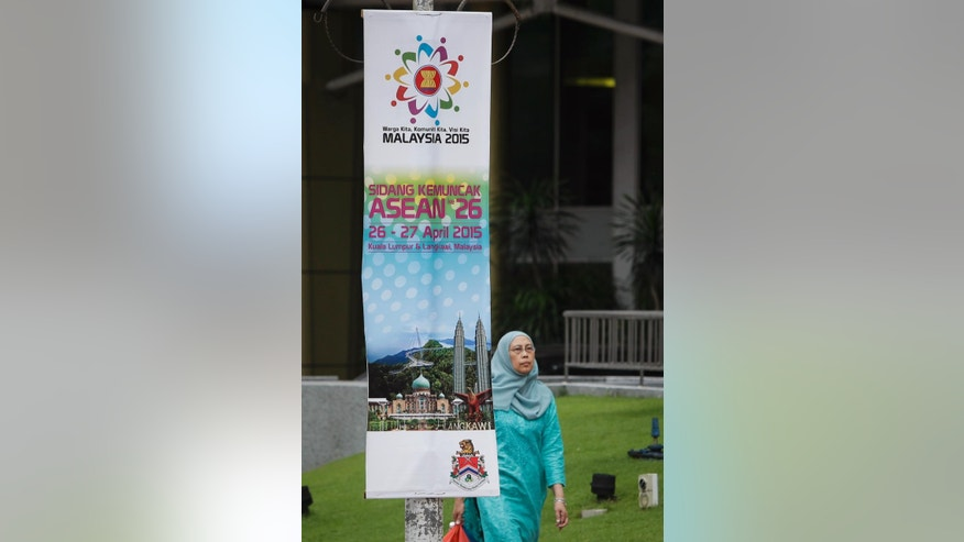 An unidentified woman walks past the banners for ASEAN Summit at the Kuala Lumpur Convention Center in Kuala Lumpur, Malaysia on Friday, April 24, 2015. The two-day summit opens on April 27. (AP Photo/Joshua Paul)