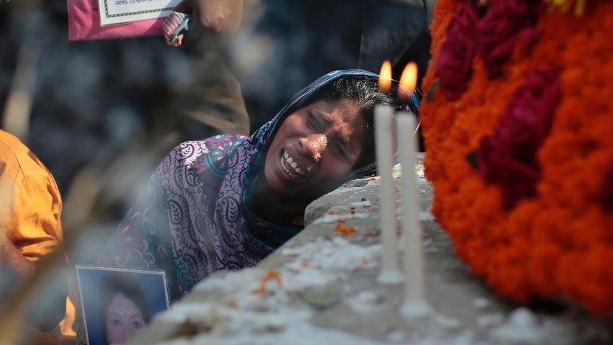 Bangladeshi relative of a victim cries in front of a monument erected in memory of the victims of Rana Plaza building collapse as they gather at the spot on its second anniversary in Savar, near Dhaka, Bangladesh, Friday, April 24, 2015. Bangladesh suffered its worst industrial disaster when Rana Plaza, an illegally built, multistoried building located outside of Dhaka, Bangladesh's capital, collapsed in 2013 killing 1,127 people and injuring about 2,500. (AP Photo/A.M. Ahad)